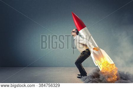 businessman with rocket on his back ready to take off. aspirations and leadership concept.