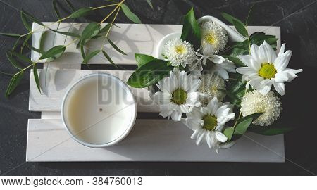 White Scented Candle And Delicate Flowers On Wooden Rack. Home Fragrances For Relaxation And Calm. F