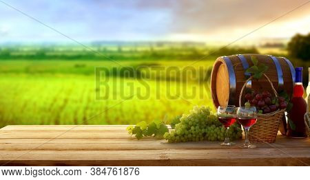 Wine and vineyard in sunset.Colorful grapes in basket. Barrel, red and white wine bottle and glass on wooden table. 