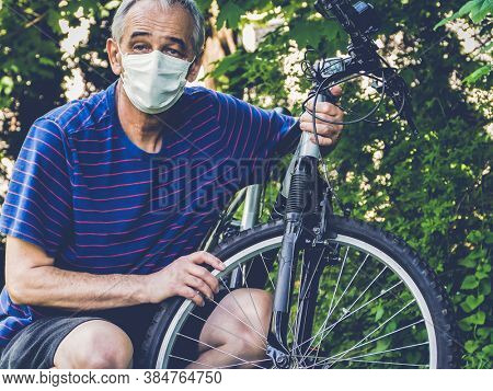 Middle age man with face mask and bike in pandemic time