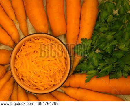 Shredded Fresh Carrots In A Bowl With Whole Carrots Around. Top View. Fresh Carrot For Backgrounds O