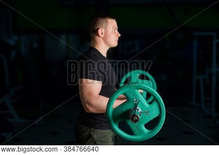 The Guy Performs The Exercise Of Lifting The Barbell For The Biceps.