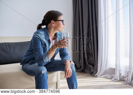 Serious Sad Middle Aged Mature Woman Sitting At Home Holding Glass Of Water Looking Out The Window.
