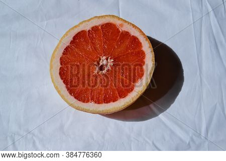 Cut Half Bright Red Orange Half Grapefruit On White Fabric With Folds In Sunlight