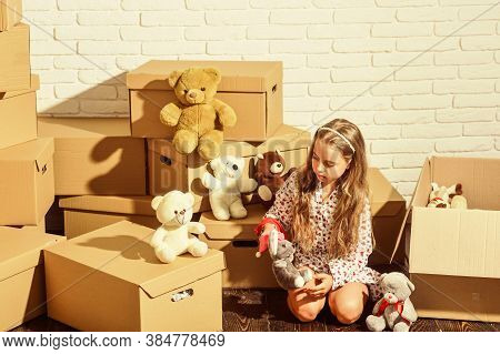 Playroom Concept. Sweet Home. Girl Child Relaxing After Unpacking Boxes. Moving In. Delivering Servi