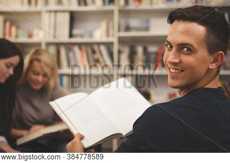 Handsome Happy Male Studenta Smiling To The Camera Over His Shoulder, Enjoying Reading A Book At The