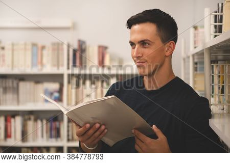 Handsome Young Man Looking Away, Smilng Playfully, Holding A Book At College Library. Attractive Mal