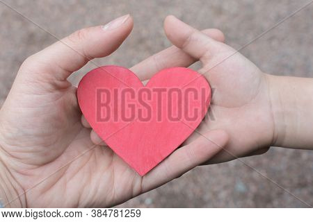 Small Wooden Heart In The Hand Of A Woman And A Child. The Concept Is A Mothers Boundless Love For A