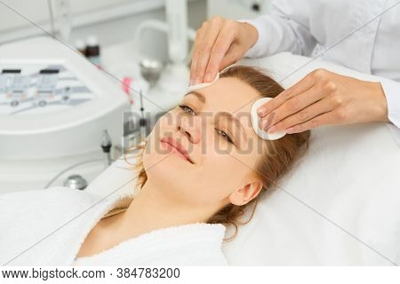 Happy Young Beautiful Woman Smiling Joyfully While Professional Beautician Cleansing Her Face With C