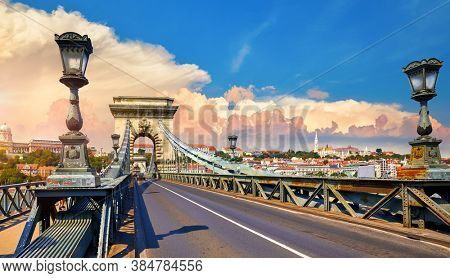 Chain bridge in Budapest, Hungary. View at Royal castle at Buda district over Danube river. Antique street lanterns along road and stone arcs. Summer urban landscape with sunset dramatic sky.