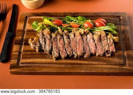 Beef Steak On A Wooden Background. Sliced Grilled Meat Barbecue Steak Strip Loin With Knife And Fork