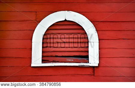 Rustic And Rotting, Arched Window Vent Is Outlined In White.  Wall And Vents Are Red.