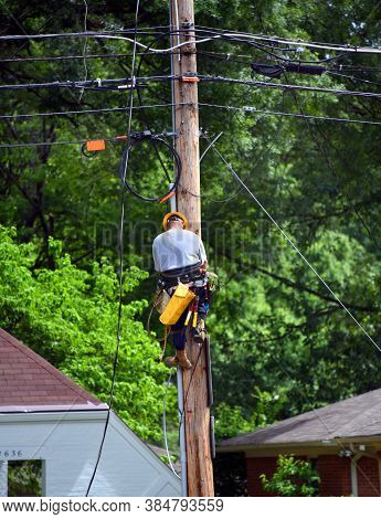 Lineman Descends Telephone Pole After Repairing A Line.  He Has On A Yellow Hard Hat And A Tool Belt