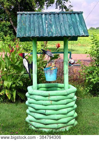 Gnome Hangs On Home-made Well House