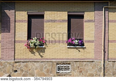 Two Windows With Closed Shutters And Bright Flowerpots. Brick Wall Of A House With Closed Windows. D