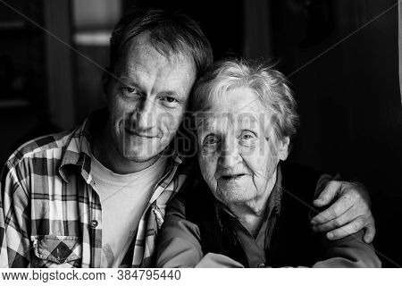 Portrait of man embracing his old grandmother. Black and white photo.