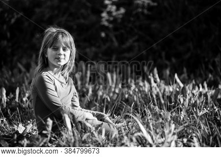 Cute little girl laying in grass in the park. Black and white photography.