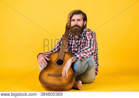 Handsome Musician Guitarist. Charismatic Mature Man Playing Guitar While Sitting. Relax With Favorit