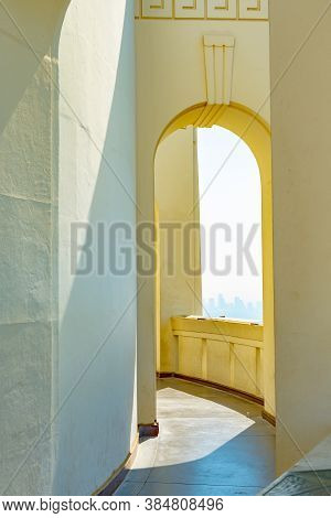 Empty Outside Corridor On Greek Design Building With Arch/ Arched Walls And City View In Background.