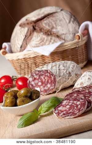 Slices Salami On Board, Cherry Tomatoes, Olivas, Bread In Breadbasket