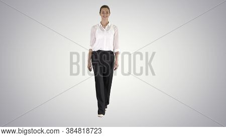 Formal Young Woman Walking And Smiling On Gradient Background.