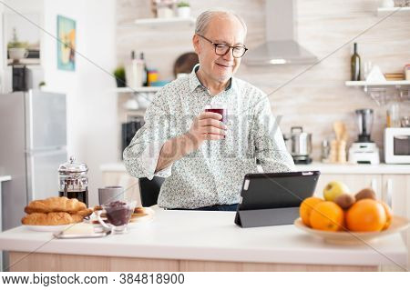 Elderly Man Using Tablet Pc In Kitchen During Breakfast Wearing Glasses. Elderly Person With Tablet