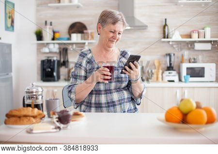 Leisure Morning For Senior Woman Using Modern Technology In Bright Cozy Kitchen. Authentic Elderly P