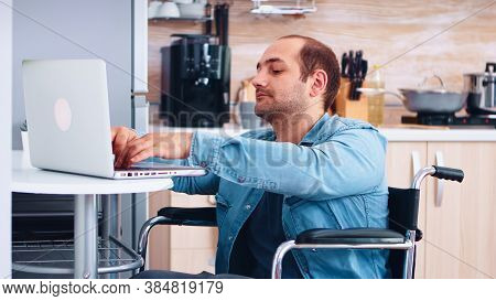 Man With Special Needs In Wheelchair Working On Laptop In Kitchen. Corporate Man With Paralysis Hand