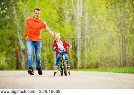 Dad Teaches Little Son To Ride Bike In Park, Keep Balance, Have Fun Family. Father Day Concept