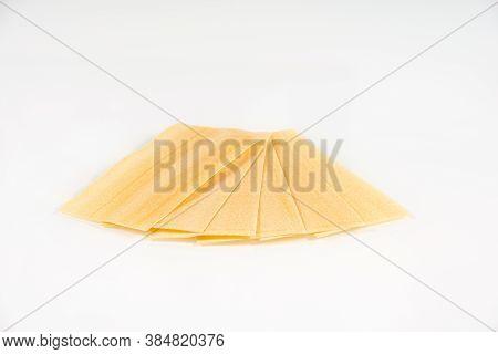 Raw Sheets Of Lasagna Pasta On A White. Pile Of Dried Lasagna Pasta Sheets