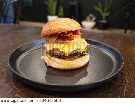 Fresh Juicy Bacon Cheese Burger On Black Plate In Restaurant