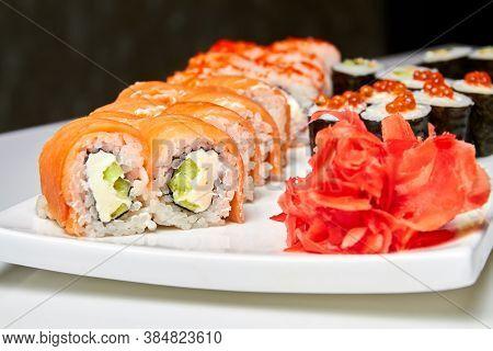 Rolls With Salmon And Cucumber, Cheese And Wasabi On A White Plate. Closeup, Selective Focus