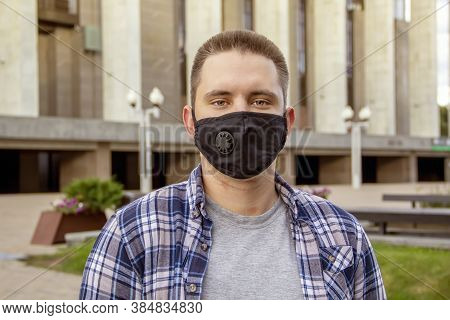 Street Portrait Of A Young Man 20-25 Years Old In A Black Medical Mask On The Background Of Modern C