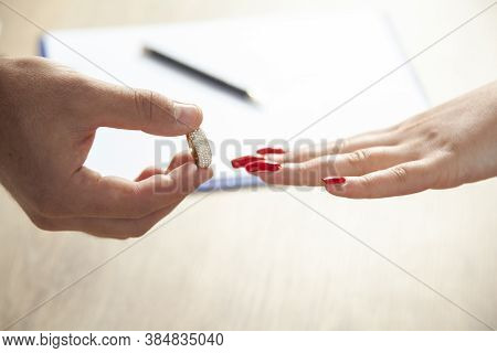 Groom Putting A Wedding Ring On The Finger Of The Bride.