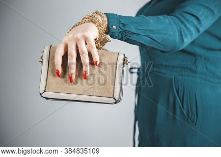 Beautiful Hand With Red Manicured Nails Holding Gold Purse Handbag On Grey Background.