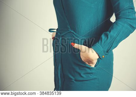 Woman Hand On Pocket On Grey Background.