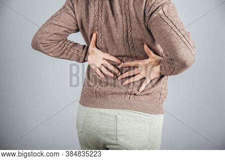 Woman Hand In Ache Back On Grey Background.