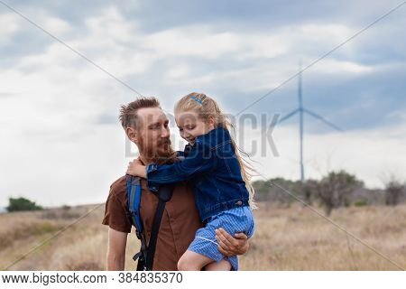Father With Daughter In Hands Standing On Hill With Nature Lanscape. Little Blonde Girl Smiling And