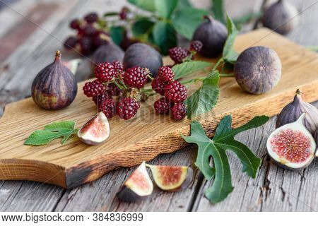 Fresh Juicy Figs And Blackberries On A Dark Background