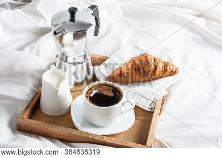 Wooden Tray With Cup Of Black Coffee, Jug Of Milk And Croissant On White Linen Bed. Breakfast In Bed