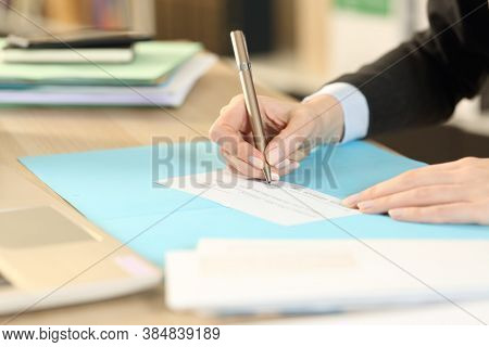 Close Up Of Self Employed Woman Hands Signing Bank Check Sitting At Homeoffice