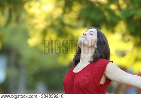 Relaxed Woman In Red Breathing Deeply Fresh Air Standing In A Park