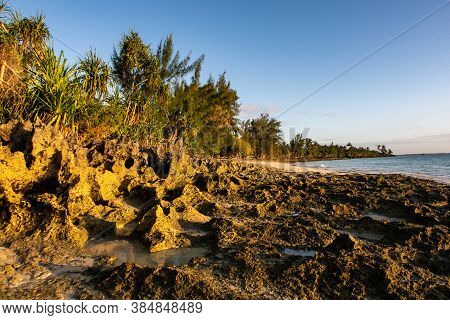 Rocky And Sandy Empty Deserted Beach With Tropical Plants And Palm Trees During Golden Hour, Before
