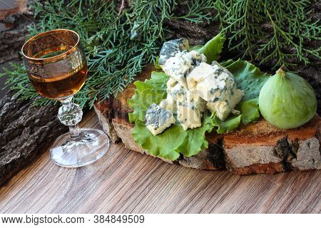 Pieces Of Blue Cheese On A Green Lettuce Leaf With Alcohol And Figs. Food On A Wooden Slice.