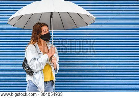 Caucasian Young Woman Standing Near Blue Grid Background With An Umbrella And Black Face Mask