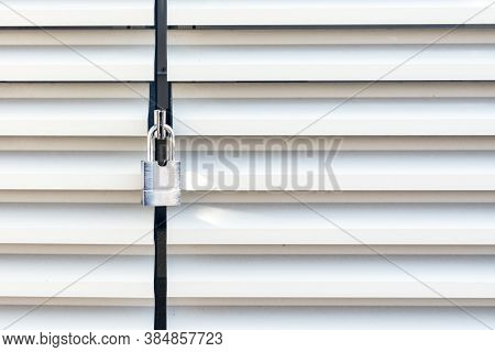 White Wavy Metal Door Of An Industrial Building With Locked Padllock During Quarantine.there Is A Ve