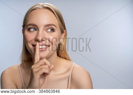 Happy Female Pressing Her Finger To Her Lips