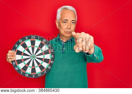 Middle age senior grey-haired man holding competition dartboard target over red background pointing with finger to the camera and to you, hand sign, positive and confident gesture from the front