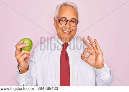 Middle age senior grey-haired nutritionist man holding healthy green apple over pink background doing ok sign with fingers, excellent symbol