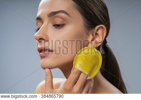 Calm Young Woman Massaging Face With Washcloth
